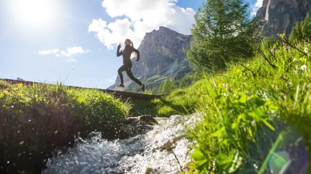vidéos et rushes de jeune femme consciente de corps exerçant, traversant un pont en bois sur le ruisseau dans le paysage vert par une journée ensoleillée, montagnes en arrière-plan - torrent
