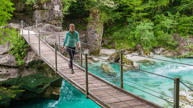 vídeos de stock e filmes b-roll de young body conscious woman hiking across a wooden bridge over mountain stream canyon in lush foliage landscape - ponte suspensa