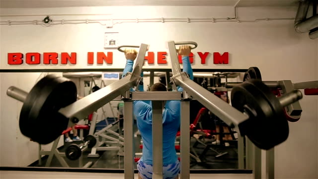 young bodybuilder training in the gym: chest - barbell incline bench press