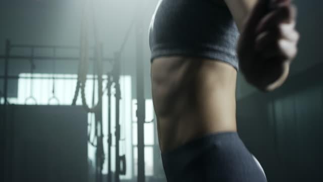Junge Bodybuilder Frau überspringen mit Springseil im Fitness-Studio