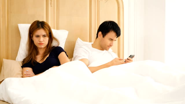Young bored couple using their mobile phone in bed