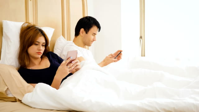 young bored couple using their mobile phone in bed - boredom stock videos & royalty-free footage