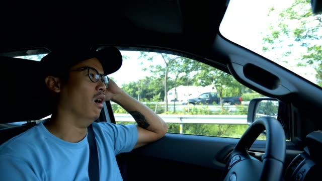 junge langweilig asiatischen mann autofahren auf verkehr stau. - feststecken stock-videos und b-roll-filmmaterial