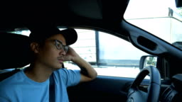 Young boring Asian man driving a car on traffic jam.