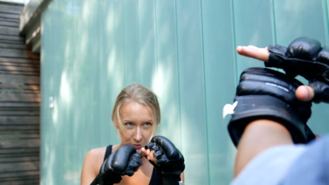 young boxer girl practices with a partner strokes. - boxing stock videos & royalty-free footage