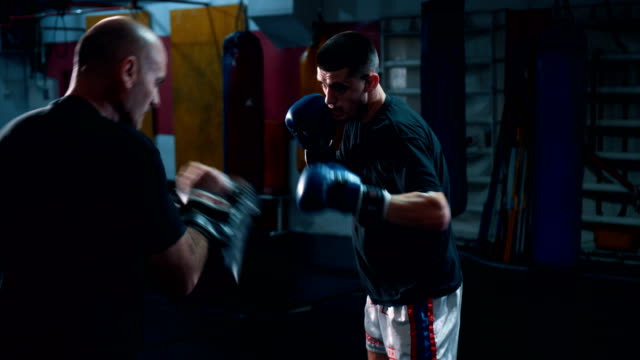 Young boxer practicing with his coach