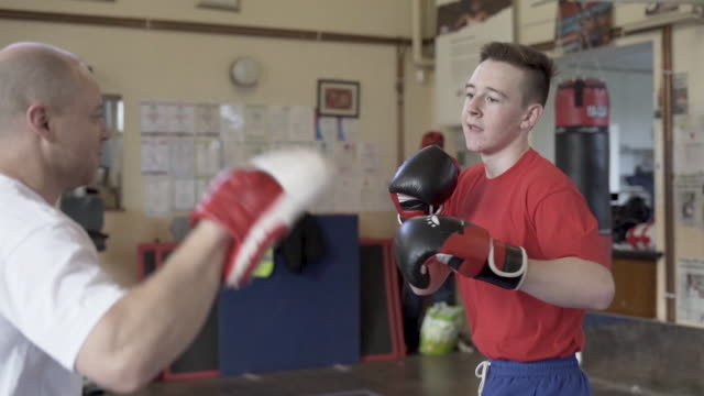 young boxer training with his coach - boxing stock videos & royalty-free footage