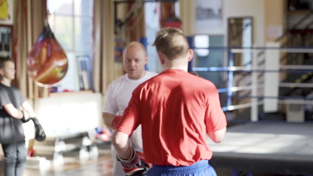 young boxer training with his coach - punch bag stock videos & royalty-free footage