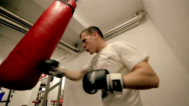 vídeos y material grabado en eventos de stock de joven boxeador con saco de boxeo en gimnasio - guante de boxeo