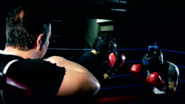 vídeos y material grabado en eventos de stock de los jóvenes boxeadores luchando en box ring - cámara de aislamiento con guantes
