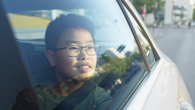 young boy 12 year old enjoys getting driven around the city on back seat of car - childhood stock videos & royalty-free footage