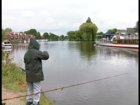 young boy adjusts his fishing line on the shore of a river as a tour boat, cliveden, passes by. - ausflugsboot stock-videos und b-roll-filmmaterial