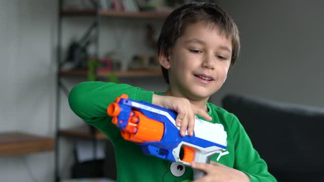 ung pojke siktar en leksakspistol mot kameran - 6 7 years bildbanksvideor och videomaterial från bakom kulisserna