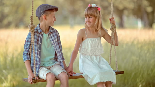slo mo a young boy and a girl holding hands on a swing - sleeveless dress stock videos and b-roll footage