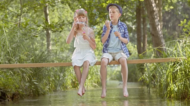 slo mo a young boy and a girl sitting on a footbridge blowing bubbles - little girls bare feet stock videos and b-roll footage