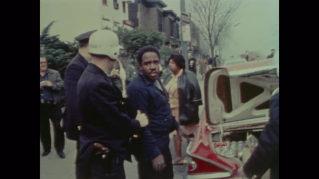 a young boy and an old woman loot from a devastated storefront as police detain search and arrest men with looted goods in the trunk of their car - 1968 stock videos & royalty-free footage