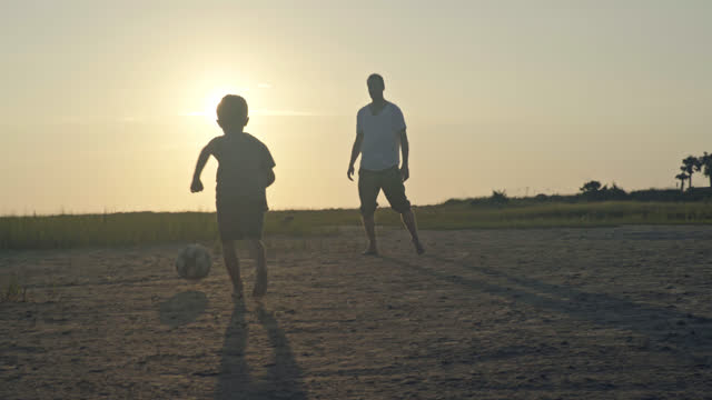 young boy and father pass and play soccer together in coastal marshland at sunrise. - アウトドア点の映像素材/bロール
