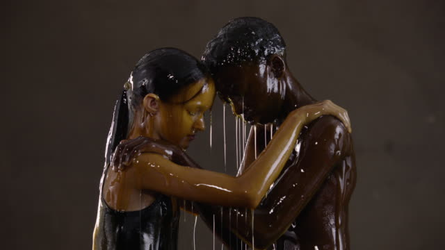 vidéos et rushes de young boy and girl drenched in honey hold each other, slow motion - perception sensorielle