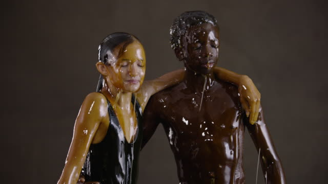 young boy and girl drenched in honey, slow motion - nur kinder stock-videos und b-roll-filmmaterial