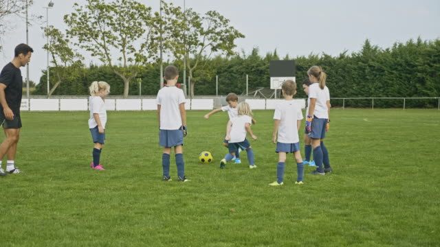 young boy and girl footballers practicing passing - sports clothing stock videos & royalty-free footage