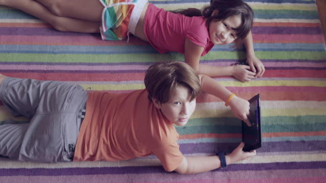 ms young boy and girl laying on carpet playing - auf dem bauch liegen stock-videos und b-roll-filmmaterial