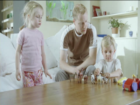 vídeos de stock, filmes e b-roll de young boy and girl play with toy cars and toy animals with their father in the living room - animal de brinquedo