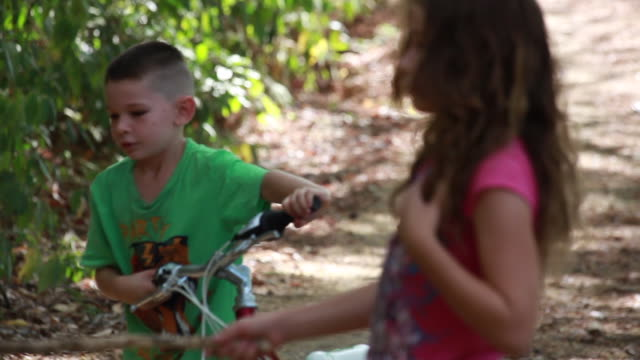 vídeos de stock e filmes b-roll de young boy and girl playing in nature throwing sticks and sharing bike - kelly mason videos
