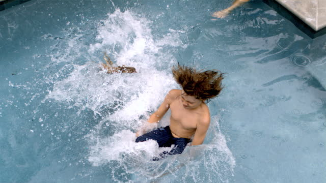 vídeos de stock, filmes e b-roll de slo mo ms pan young boy and girl running by woman and jumping into swimming pool/connecticut, usa - vadear