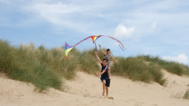 a young boy and girl running on a beach through the sand dunes flying their kites. - kid with kite stock videos & royalty-free footage
