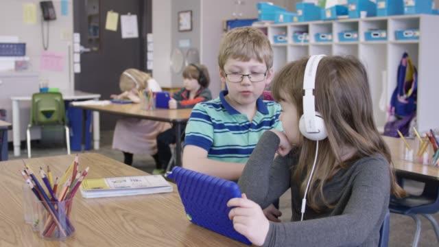vídeos de stock e filmes b-roll de young boy and girl sharing a tablet in school - escola primária