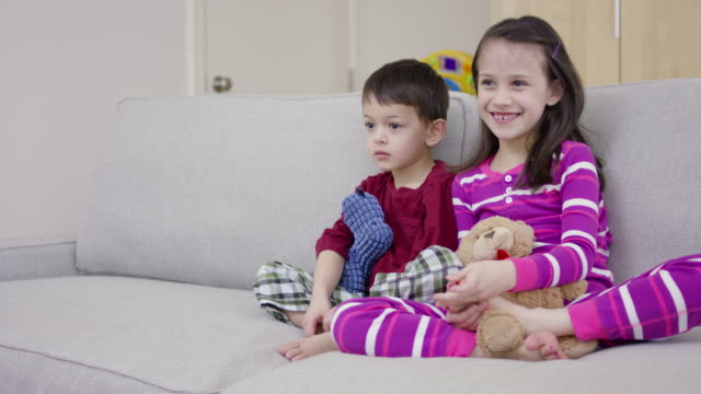 Young boy and girl, sitting on couch and watching television