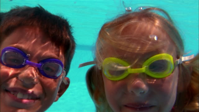 a young boy and girl wearing goggles smile and wave underwater. - swimming goggles stock videos & royalty-free footage
