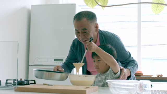young boy and his grandfather cooking together - pancake stock videos & royalty-free footage