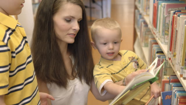 cu young boy and his little brother flipping through childrens books at public library while mom looks on / rancho mirage, california, usa - messa a fuoco video stock e b–roll