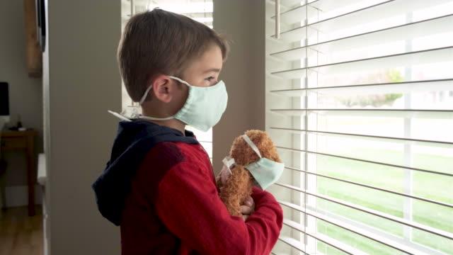 stockvideo's en b-roll-footage met jonge jongen en zijn teddy die gezichtsmaskers dragen - vermijden