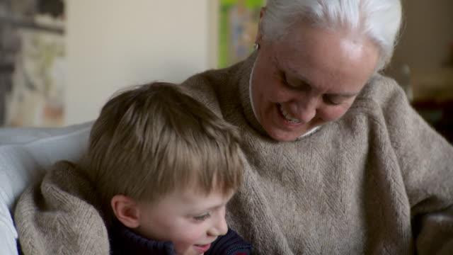 vídeos y material grabado en eventos de stock de ms cu td young  boy and older woman playing on tablet computer / stowe, vermont, united states - nieto