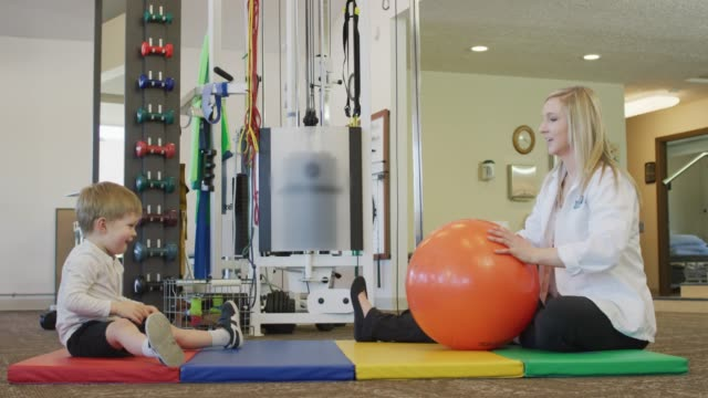 young boy and physical therapist roll a ball - fatcamera stock videos & royalty-free footage