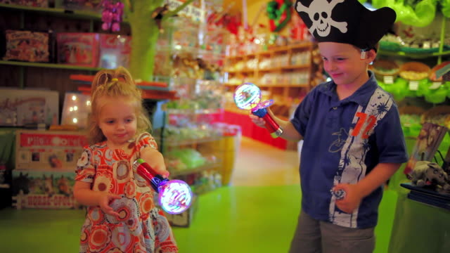 Young boy and young girl hold spinning lights in toy and candy shop