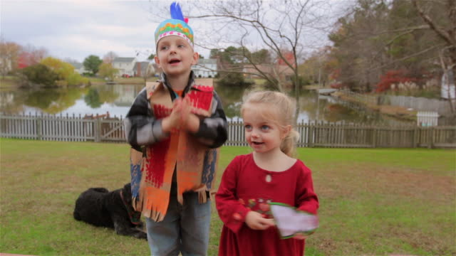 young boy and young girl perform a thanksgiving song in backyard - vignette stock videos & royalty-free footage