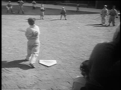 b/w 1941 rear view young boy at bat hits ball + runs in little league baseball game / nyc / newsreel - baseball bat stock videos & royalty-free footage