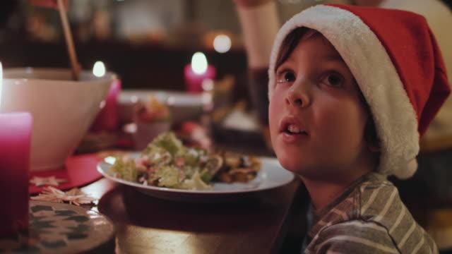 vídeos de stock e filmes b-roll de young boy at christmas dining table - natal