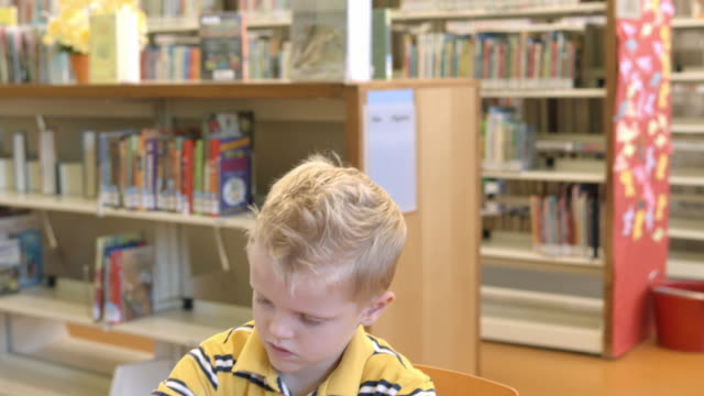 cu pan young boy at kids table in childrens section of public library playing with puzzle / rancho mirage, california, usa - rancho mirage stock videos & royalty-free footage