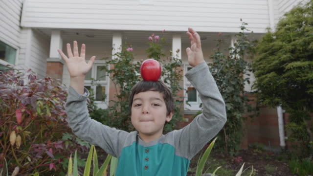 young boy balancing apple on his head - saggezza video stock e b–roll