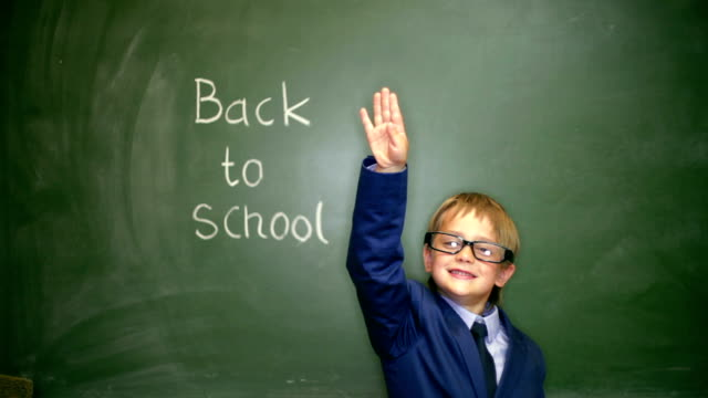 Young boy behind the blackboard, back to school