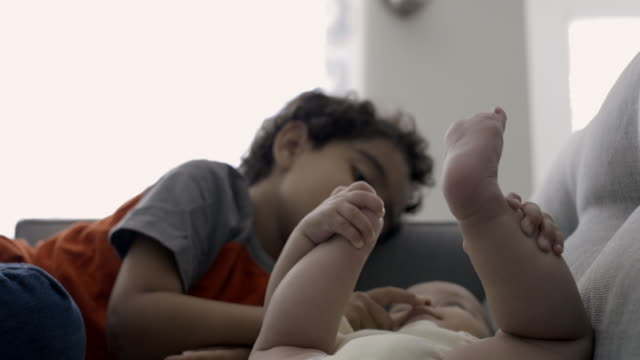 young boy being tender with his baby brother on sofa. - sibling stock videos and b-roll footage