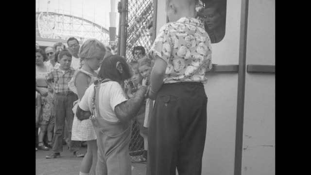 vidéos et rushes de a young boy blond girl and clothingwearing chimpanzee albert arrive at the park and buy numerous tickets that soon festoon the chimp's neck - chimpanzé