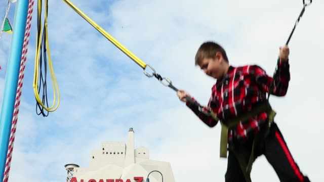 stockvideo's en b-roll-footage met a young boy bounces on a bungee trampoline at pier 39 on march 11 2015 in san francisco california - pier 39