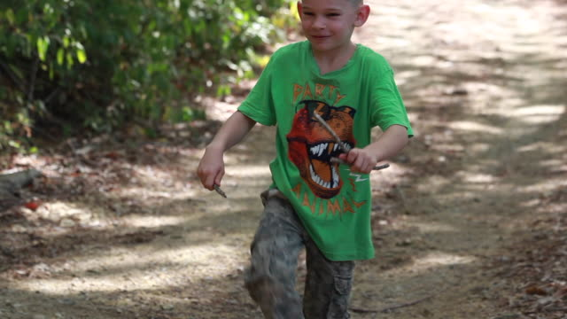 vidéos et rushes de young boy breaks branch on his leg then tosses the sticks and walks away smiling - t shirt