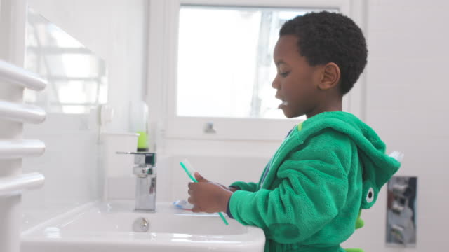 vidéos et rushes de young boy brushing his teeth - lavabo