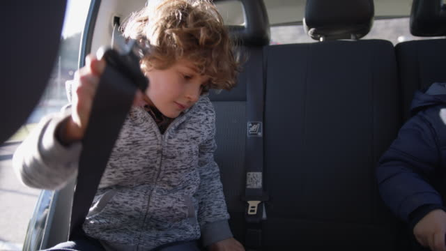young boy buckles seat belt in car - seat belt stock videos & royalty-free footage